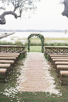 Let the naturally beautiful setting of your venue dictate your ceremony decor and keep things simple with a classic floral arch and linen-upholstered wooden benches.