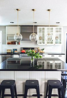 "Cedar & Moss Brass Alto Pendants with Clear 10"" Globes over a Timeless Kitchen Island"