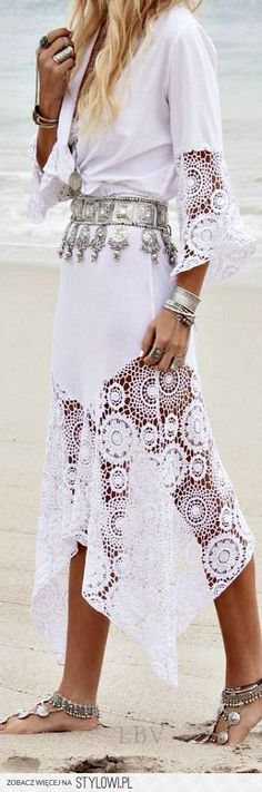 Pretty crocheted insets on the sleeves and skirt of this striking white dress ...