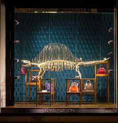 LOUIS VUITTON's gilded dinosaur bone window installation, drawing historical reference from the remains on display at the natural history museum in paris's les jardins des plantes, french fashion house New York 5th avenue maison store front.