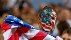 A USA fan cheers on the team at Beach Volleyball  A United States fan with her face painted in the stands during the Women's Beach Volleyball on Day 12.