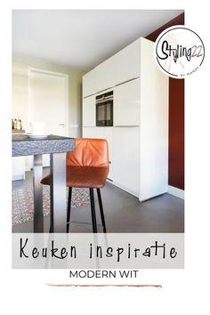 Witte keuken met warme kleur op de muur. Portugese tegels in de strakke vloer. Rode kleuren met zwarte accenten.  Strakke keuken, wit, modern, tegels en bar.  Wil je ook kleuraccenten in de strakke keuken? Styling22 heeft altijd leuke keuken ideeen.