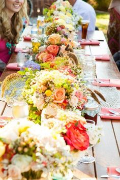 colorful flowers as centerpieces in a communal table at the wedding reception