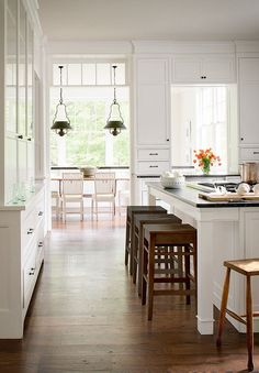 The cabinets in this #modern #kitchen create a clean look with Benjamin Moore's Simply White paint.
