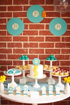 yellow and turquoise rock and roll baby shower dessert table with record backdrop