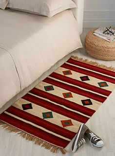 A rug with raw and natural texture, woven in 100% wool with stripes and diamonds in accent rich warm colours.    An ethnic touch to your decor   Twisted fringes on the trim   70 x 140