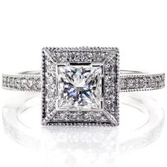 Diamond engagement ring has modern, sleek straight lines. The princess cut center stone is surrounded by a square halo, which mimics its shape, and a simple band. Both the halo and band are done in micro pave. Princess Amante from Knox Jewelers #halo #princesscut