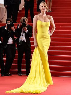 CHARLIZE THERON commanding the red carpet platoon in canary yellow Dior Haute Couture gown