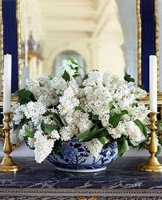 White lilacs in a blue and white bowl with brass candlesticks - Carolyne Roehm