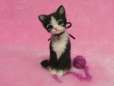 This soft black (very dark gray) & white kitten is so soft, needle felted of a variety of wool.  The paws are very small, but they have cute