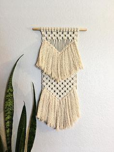 This macrame wall hanging is handmade with 1/8 organic cotton rope, cotton fringe, and a 12 x 1/2 wooden dowel. The wall hanging measures 12 across and approx. 22 down. This small macrame wall hanging is the perfect way to add some texture to any wall! Hang it as a single piece of