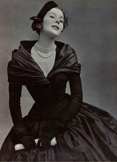 1951  Christian Dior  exécute en taffetas noir de ducharne le fichu drapé sur les épaules et la jupe corolle qui contrastent avec la rigueur du corsage de lainage d'un noir mat, au grand décolleté, aux manches longues et collantes, à la courte