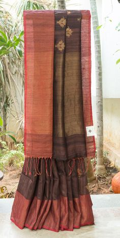 CHARMING COFFEE BROWN WITH BLACK HALF AND HALF BAILOU MATKA SILK HAS JAMDANI GOLD ZARI BUTTAS.THE DARK RED WITH GOLD ZARI BORDER AND PALLU GIVES THE SAREE A GLAMOROUS FINISH.