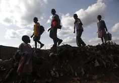 Children walk on a mound of garbage on their way home from school in the slum of Kawangware in Nairobi (Reuters)