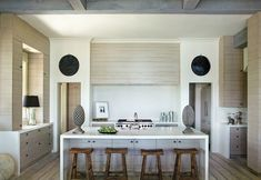 summerour architects via design chic.  Check out the horizontal wood slats hiding the rang hood.