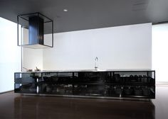 Japanese designer Tokujin Yoshioka has developed a transparent modular kitchen system with smoked-glass surfaces that display the tools inside.