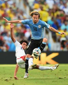 Yeltsin Tejeda of Costa Rica tackles Diego Forlan of Uruguay during the 2014 FIFA World Cup Brazil Group D match between Uruguay and Costa R...