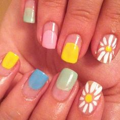 This colorful manicure features sunny colors in blue, yellow, green and pink nail polish accentuated by white daisies. Discover the products used in this nail art design and get inspired.