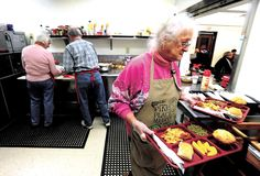 Salvation Army soup kitchen manager Barbara Patterson serves lunch with volunteers Bob and Lorraine Hooley of Dover Alliance Church on Tuesday at the New Philadelphia facility.