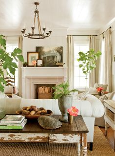 What charm this cottage living room exudes with all the fabrics in neutral tones, and accents adding the punch.  @Barbara Wirth Art loves the art propped on the mantel.  Yes, charming!