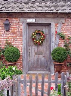 A rustic-looking brick house with a wooden door is made even more charming with an autumn wreath.