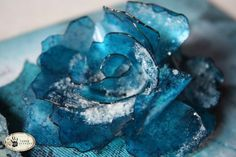 The shaped rose was created using Wendy Vecchi's Clearly For Art clear molding film. I cut three flowers using the Tim Holtz Alterations Tattered Florals die. I colored the flowers using an assortment of alcohol inks in different shades of blues. I then shaped and layered the flowers using the process I show in my Shaped Roses tutorial