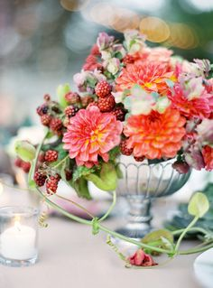Jose Villa Chestnut and Vine Floral Design, Silver compote with a flower arrangement of orange dahlias and raspberries
