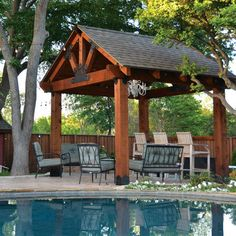 This image features a pool pavilion built using the Post Base Kit, Truss Base Fan, Laredo Sunset Truss Tie Plate, and Truss Accents by OZCO Ornamental Wood Ties