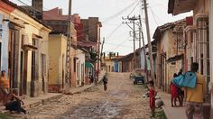 Normal run down street in Cuba with lots of people sitting on their door steps