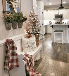 Farmhouse Christmas entryway decor, flocked tree, white pew bench, red plaid blanket, chippy white C