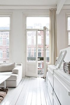 Light-filled, all-white living space looking out to the balcony