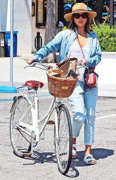 Jessica Alba wears a striped tank top, denim shirt, cuffed pants, Birkenstocks, a straw fedora, and mini bag