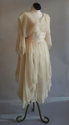 Whimsical & romantic vintage wedding dress circa 1919. Middy style bodice, handkerchief sleeves,waist sash & billowed below the knee skirt. Perfect for a garden wedding. Designed by: handmade Made of: