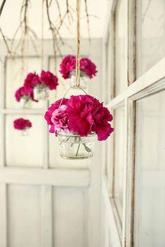 Hot pink hanging flower arrangements in glass jars! So cool!