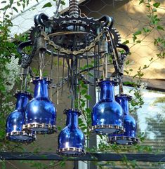Outdoor chandelier made with cut glass bottles and recycled bicycle parts. Beautiful!