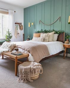 DIY Board and Batten Wall Treatment in our Master Bedroom | Anita Yokota | A modern decorating twist on the classic board and batten look! On the blog, I'm showing you the reveal of our new wall in our boho chic master bedroom with an earthy green wall paint and gold sconces. #masterbedroom #walltreatments #boardandbatten