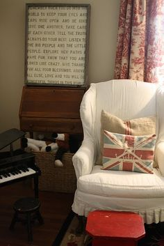 Another great wingback with fantastic pillows.  Somehow reads modern despite the toile curtains - b/c of the red stool, perhaps.