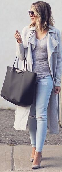 A woman is wearing a long gray trench coat, light blue distressed denim jeans, a gray t-shirt, gray shoes and a big black bag