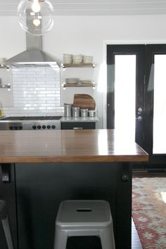 kitchen features black ikea kitchen cabinets ikea ramsjo cabinets accented with ikea varde handles paired with kashmir white granite countertops and