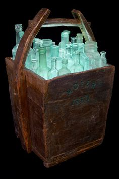 """Glassket""    An ongoing series combining wooden containers such as shipping crates, buckets and footlockers filling them with glass containers. These bouquets of tightly arranged bottles are illuminated a bright, cool blue from below. (Avg. w:14"" h:22"" d:11"")    $865.00 and up"