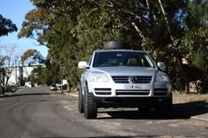 Custom Touareg with large mud tiers and spare tire roof rack.