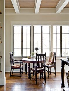 An antique table and chairs sit in front of the old casement windows, with wavy glass.