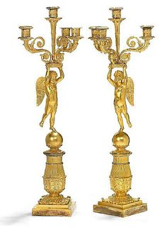 A pair of Charles X gilt bronze candelabra, adorned with put