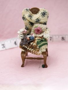dolls house chair of a little old lady complete with tea and biscuits, knitting and crocheted bits.