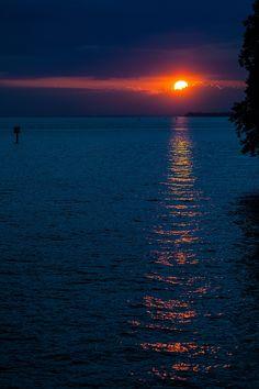 Von der kleinen Insel den Sonnenuntergang überm See