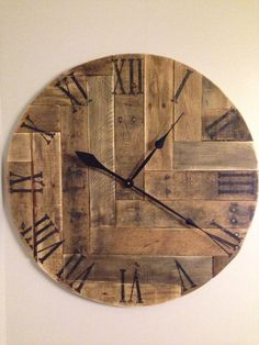 This decorative rustic wood clock has been made from reclaimed pallet boards. It has been arranged in a herringbone design and would make a great addition to your home decor! The roman numerals have been painted black and distressed. It measures 24 in dia