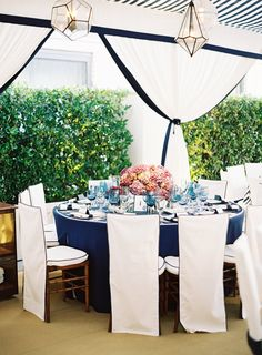 We love these unique light fixtures & the simplicity of the table linens! Photography: Jose Villa Photography. Read More: https://www.insideweddings.com/weddings/incredible-rooftop-rehearsal-dinner-with-striking-striped-tent/555/