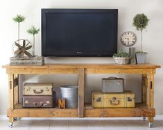 Rustic table under mounted tv, yes please!, love the vintage luggage as decor too !