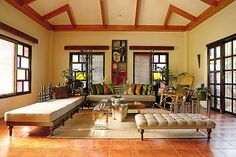 The stained glass windows that were once part of an old mid-century church can be seen in this living area. Except for the tumba-tumba or rocking chair,�the furniture pieces were designed by Gwyn and built by Asian Tropical Lifestyle in Pampanga.