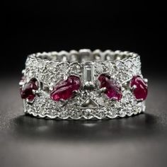 Wide and wonderful, this striking, original Art Deco eternity wedding band, hand fabricated in platinum, circa 1925, sparkles all around with tiny single-cut diamonds punctuated with straight baguette diamonds and a central row of carved rubies. Ring size 6 1/2.